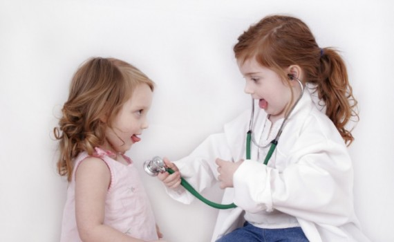 Little girl with stethoscope listening to her sister's heart
